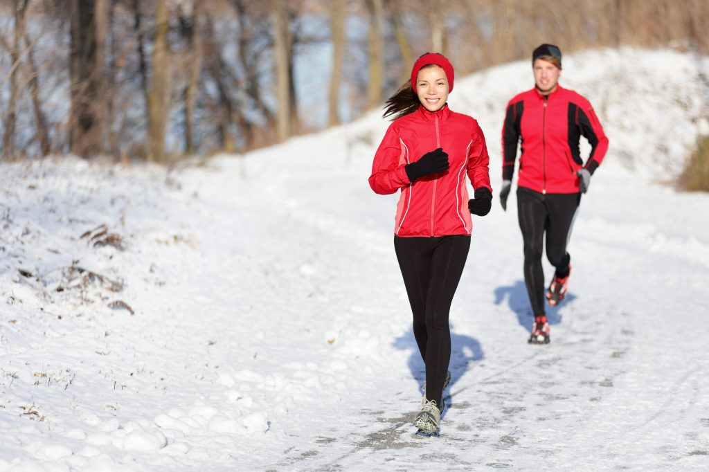Winter running exercise couple. Runners jogging in snow. Young asian woman fitness model and caucasian man.Sport couple running in winter.