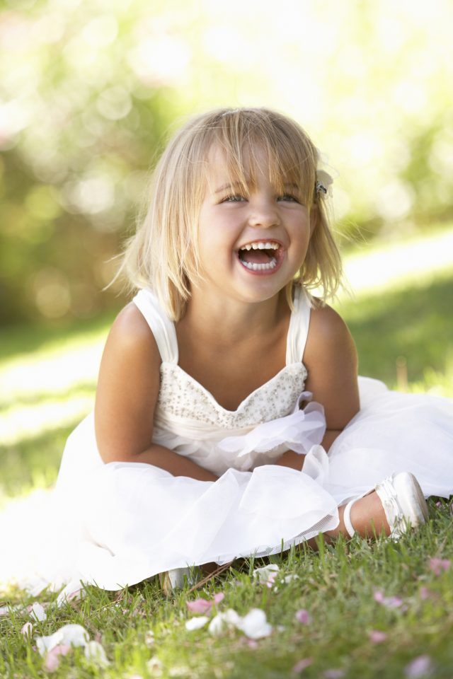 Young girl sitting in park laughing
